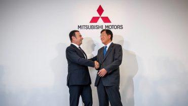 Carlos Ghosn of Renault-Nissan shakes hands with Osamu Masuko of Mitsubishi.