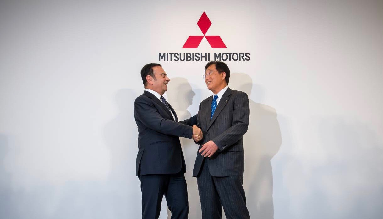 Carlos Ghosn of Renault-Nissan shakes hands with Osamu Masuko of Mitsubishi.