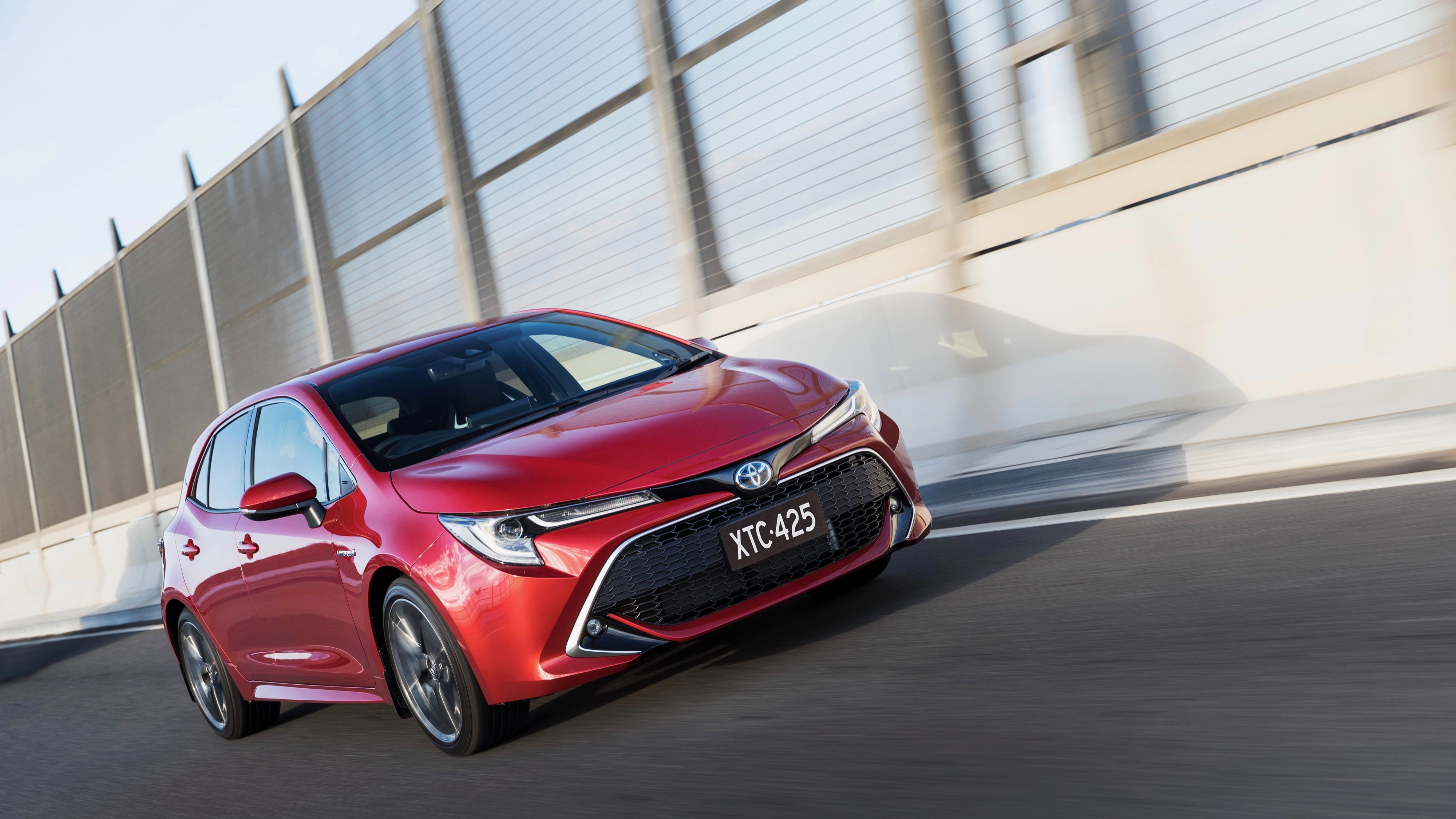 2019 Toyota Corolla ZR hybrid Volcanic Red front 3/4 driving