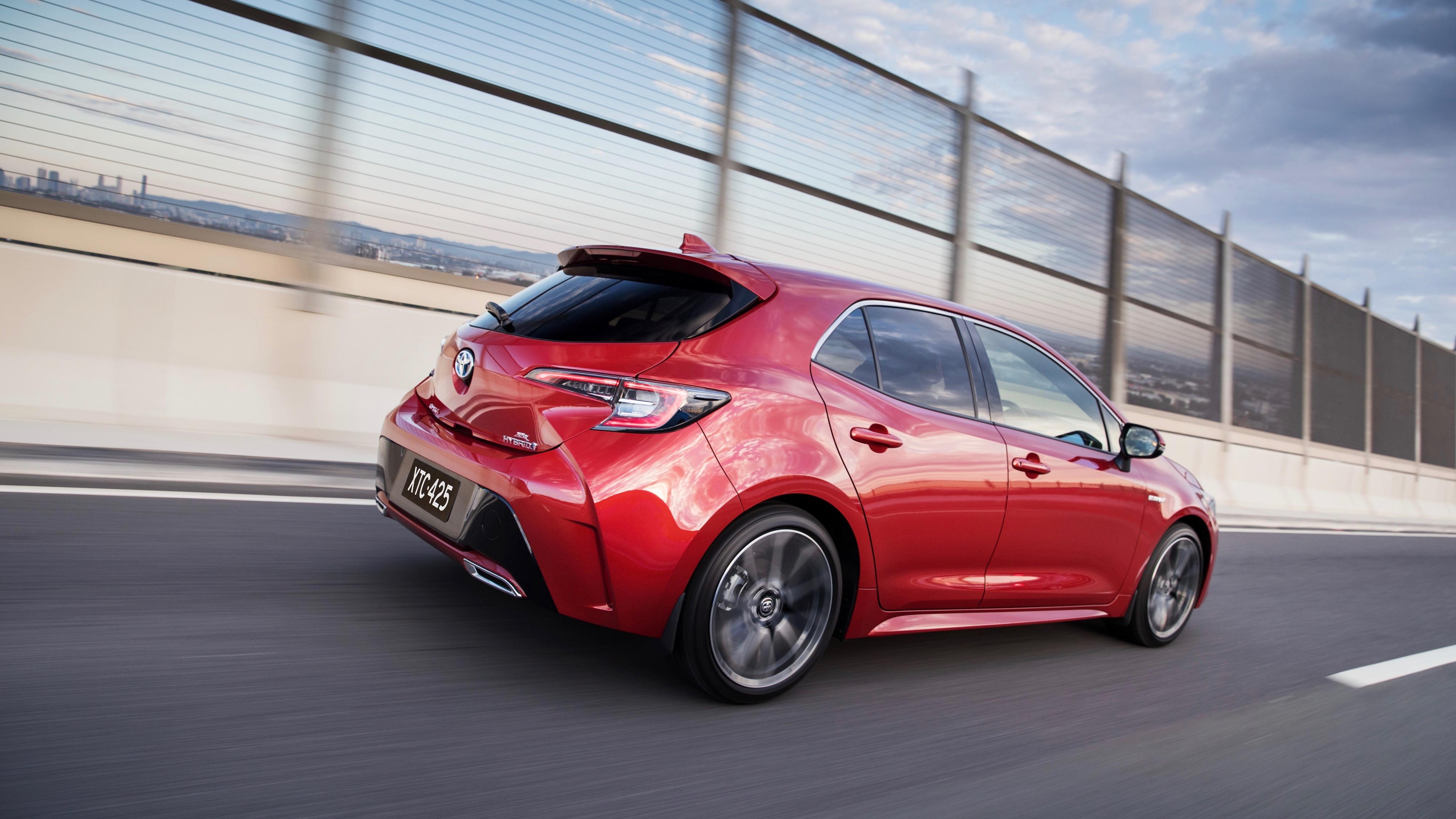 2019 Toyota Corolla ZR hybrid Volcanic Red rear 3/4 driving