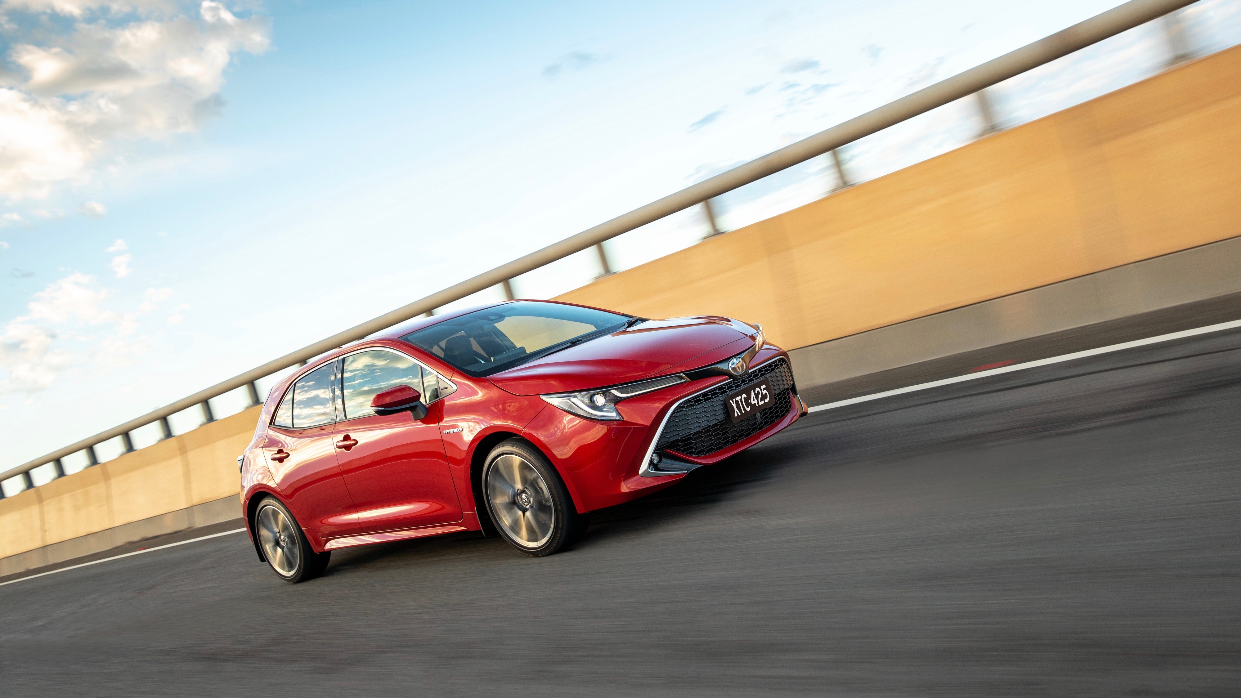 2019 Toyota Corolla ZR hybrid Volcanic Red side 3/4 driving